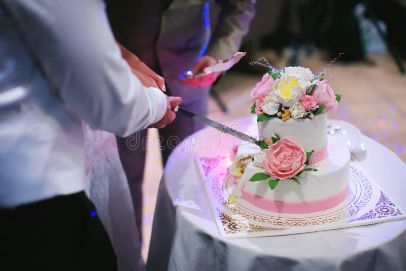 Die Braut und der Bräutigam schnitten die Hochzeitstorte stockfoto