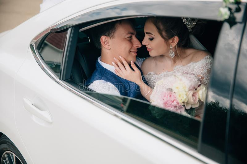 Die Braut und der Bräutigam sitzen im Rücksitz des Autos, das Mädchen hält einen Blumenstrauß von Blumen in ihren Händen lizenzfreies stockbild