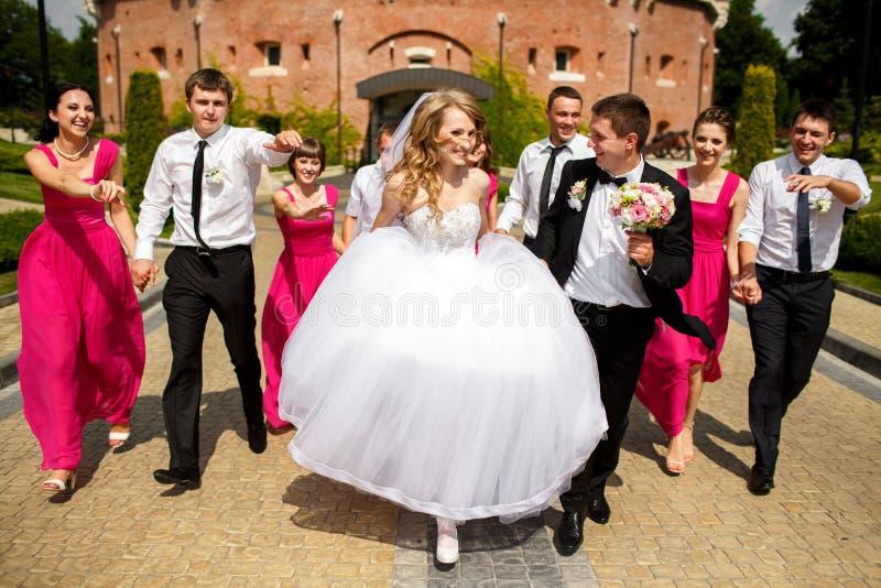 Die Brautjungfern und Groomsmen haben Spaß gehend um den Park mit stockfoto
