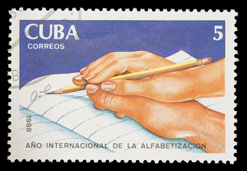 Die Briefmarke, die in Kuba gedruckt wird, zeigt eine Hand, die jemand anderes hilft zu schreiben, internationales Bildungsjahr stockbilder