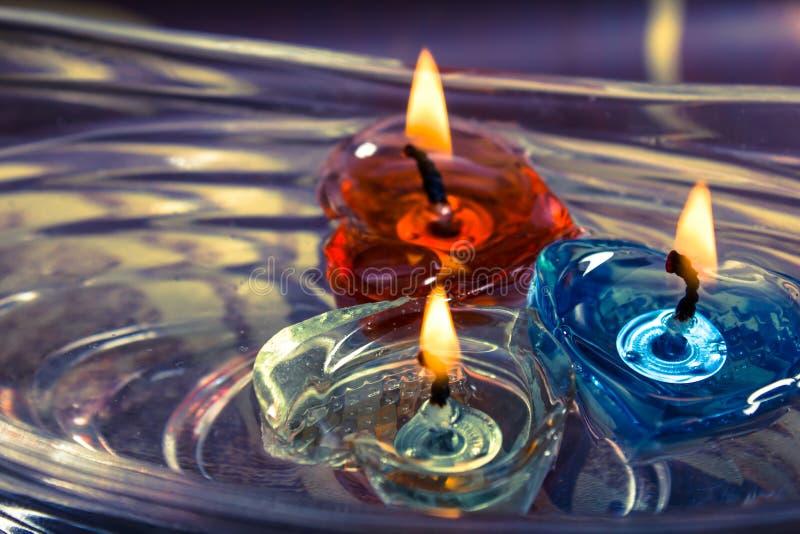 Die bunten drei Kerzen, die auf Wasseraroma schwimmen, rollen, Retro- lizenzfreie stockfotografie