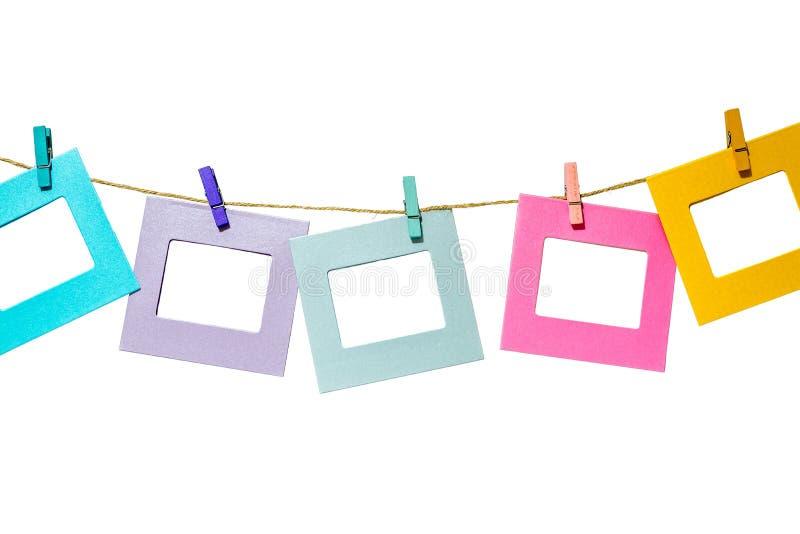 Die bunten lustigen Bilderrahmen, die an einem Seil mit Wäscheklammern hängen, twine lokalisiert lizenzfreie stockfotografie