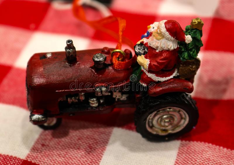 Die cast santa on tractor with Christmas tree ornament. Sitting on red and white checkered tablecloth stock image