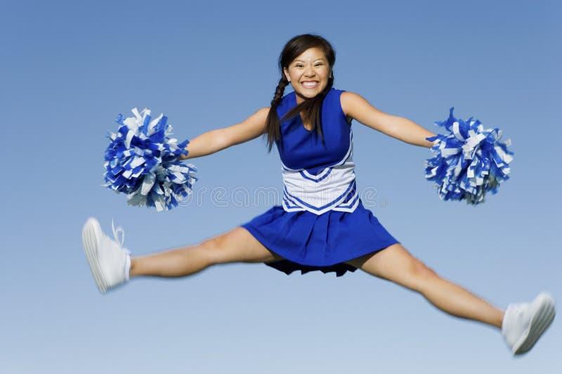 Die Cheerleader springend mit Pom-Poms lizenzfreies stockbild