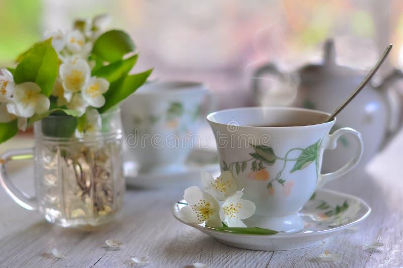 Die chinesische Teekanne des Lehms, zwei Cup und Zucker auf einer hölzernen Tabelle Schalen mit Tee und einem Vase mit einem Jasm lizenzfreie stockbilder