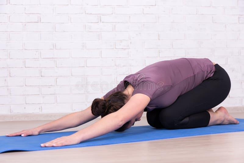 Die dünne Frau, die Sport tut, trainiert über weißer Backsteinmauer stockbild
