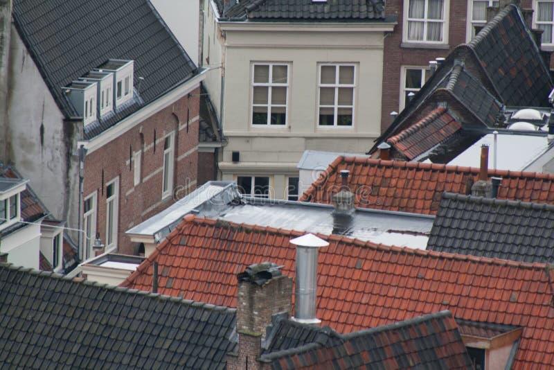 Die Dachspitzen mit vielen roten und schwarzen farbigen Fliesen und Kaminen in einer europäischen Stadt im netherland stockbilder