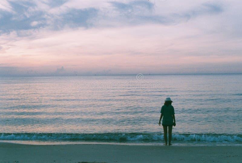 Die Dame, die entlang Strand geht stockbilder
