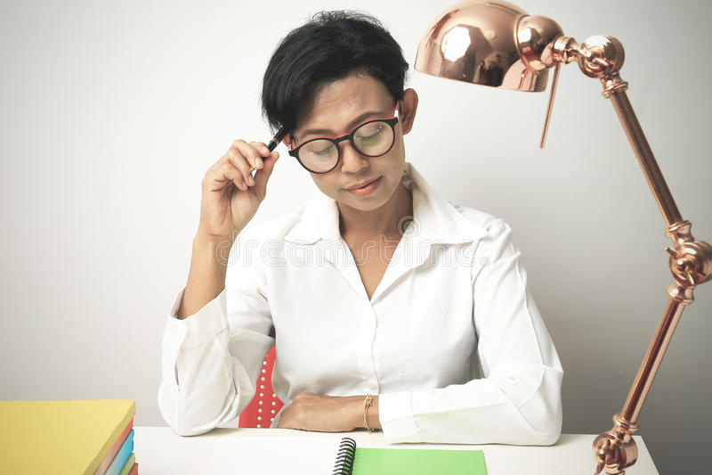 Die denkende Frau und lassen einen Stift und einen Notizblock setzen stockfotos