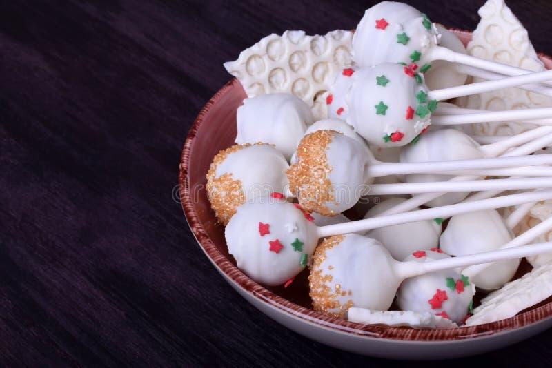 Die in der weißen Schokolade umfassten und mehrfarbigen Kuchenknalle besprüht lizenzfreies stockbild