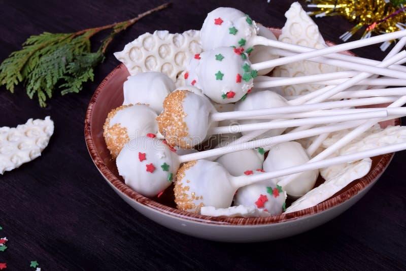 Die in der weißen Schokolade umfassten und mehrfarbigen Kuchenknalle besprüht lizenzfreies stockfoto