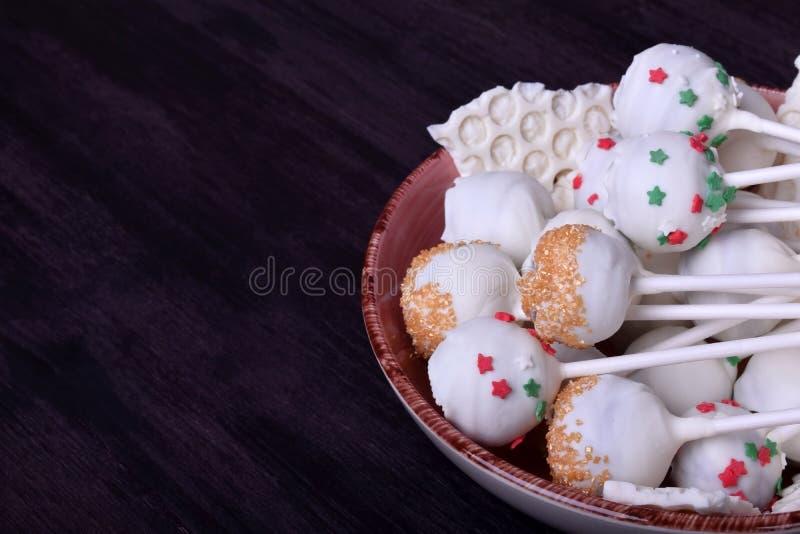 Die in der weißen Schokolade umfassten und mehrfarbigen Kuchenknalle besprüht stockfotografie