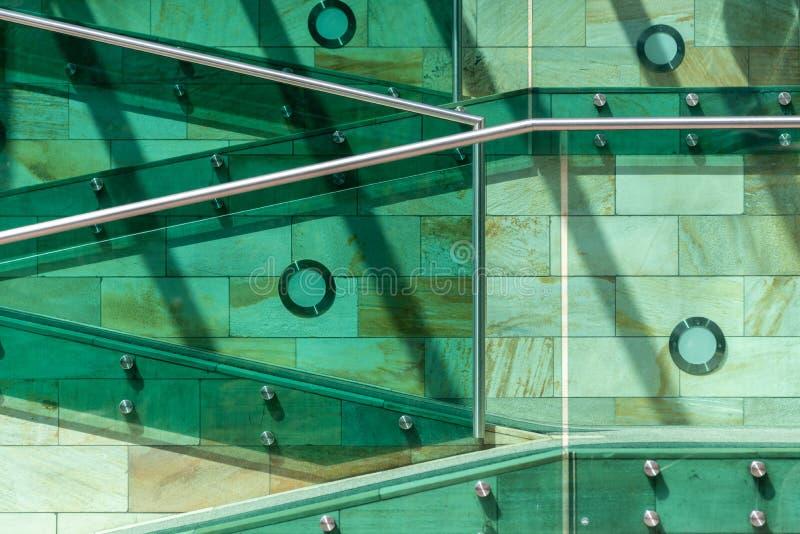 Die Details der modernen Architektur Treppe in den grünen, orange und gelben Farben, gemacht vom Stein, vom Glas und vom Metall stockbild