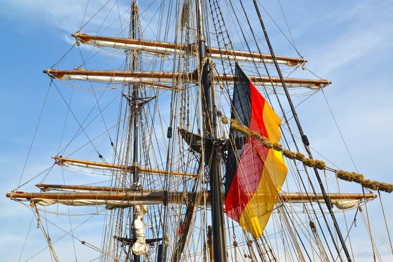 Die deutsche Flagge flattert auf einem Mast des Segelschiffs stockfotos