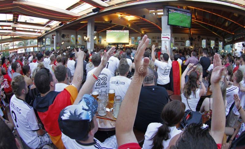 Die deutschen Fans, die Fußballweltcup aufpassen, passen auf einer gedrängten Terrasse während ihrer Feiertage in Mallorca zusamm stockfotos