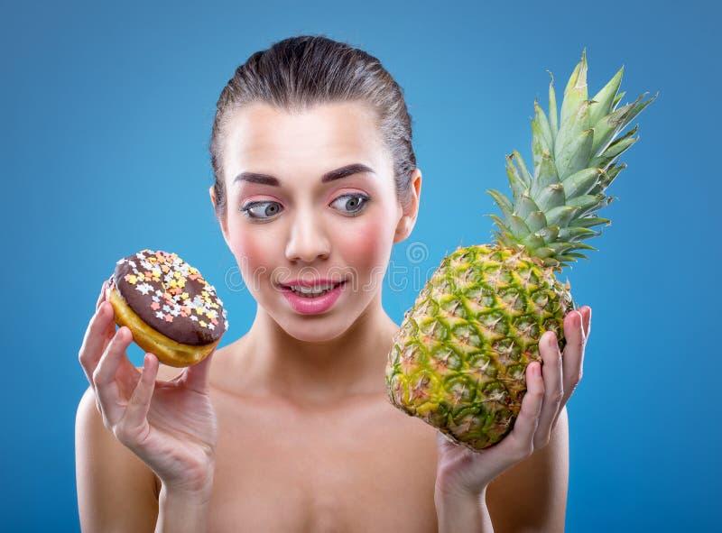 Die Diät der Frauen Donut oder Ananas? stockfotografie