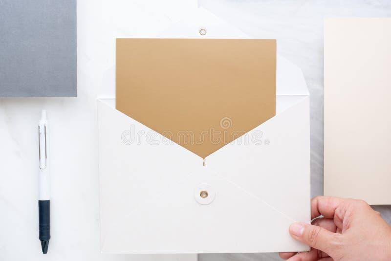 Die Draufsicht der Hand leere goldene Karte im Weiß halten schlagen auf t ein stockfotos
