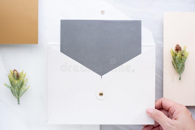 Die Draufsicht der Hand leere graue Karte im Weiß halten schlagen mit p ein stockfotografie