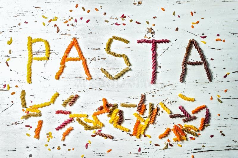 Die Draufsicht des Wortes TEIGWAREN, geschrieben in ein mehrfarbiges fusilli gemacht von der Weizenpaste, auf einem weißen hölzer stockbild