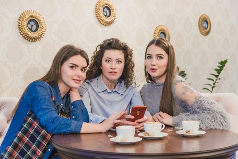 Die drei besten Freunde kamen, Kaffee und Klatsch zu trinken Mädchen sind Spaß und Lachen Mädchen mit dem schönen schwarzen Haar lizenzfreie stockfotos