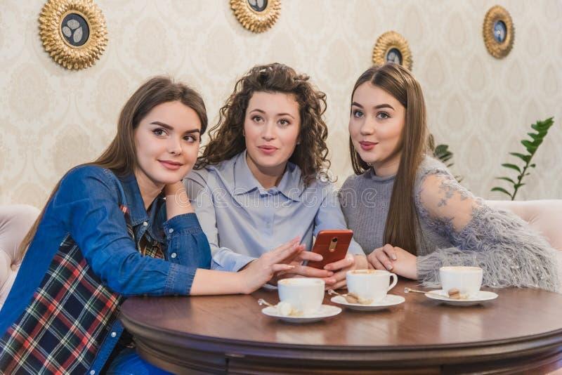Die drei besten Freunde kamen, Kaffee und Klatsch zu trinken Mädchen sind Spaß und Lachen Mädchen mit dem schönen schwarzen Haar lizenzfreie stockbilder