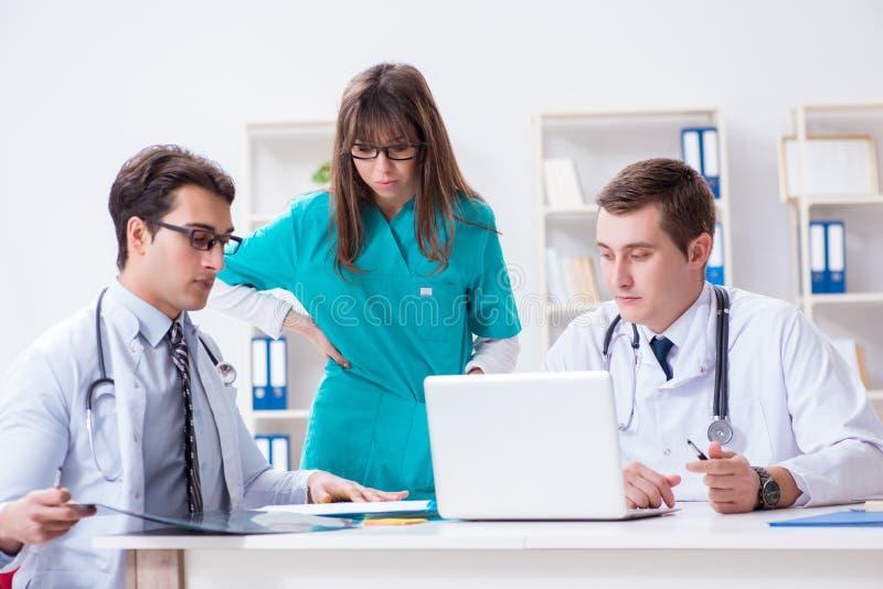 Die drei Doktoren, die Scan-Ergebnisse des Röntgenstrahlbildes besprechen lizenzfreies stockbild
