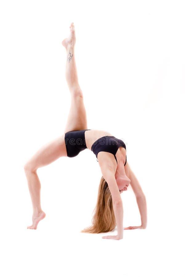 Die duktile flexible schöne junge Frau macht die athletischen, gymnastischen Übungen in Krabbenposition lokalisiert auf weißem Hi stockfotografie