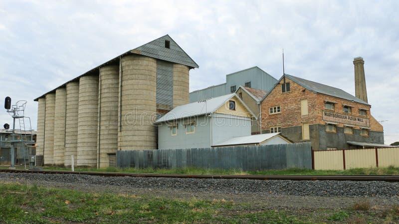 Die ehemalige Getreidemühle 1881 ist ein drei-storeyed Backsteinbau mit einem abgetrennten Eisenlagerschuppen und konkreten Silos stockfotos
