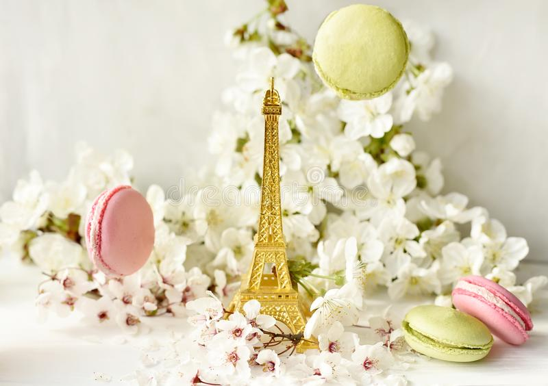 Die Eiffelturmfigürchen unter weißen Kirschblumen und süßen mehrfarbigen Makronen Liebe, Romanze, Frühling stockfoto