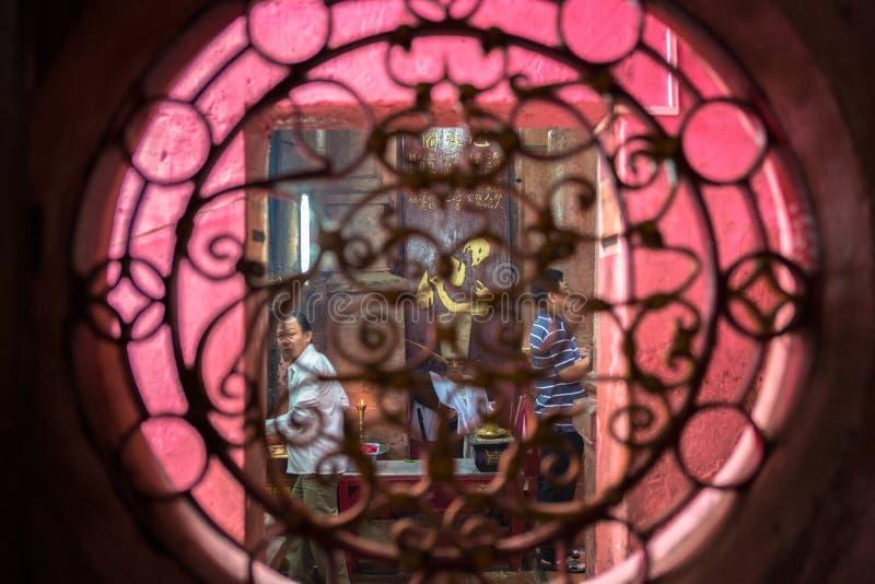Die eifrigen Anhänger, die durch künstlerisch geschnitztes Fenster gesehen werden, beten bei Jade Emperor Pagoda lizenzfreies stockfoto