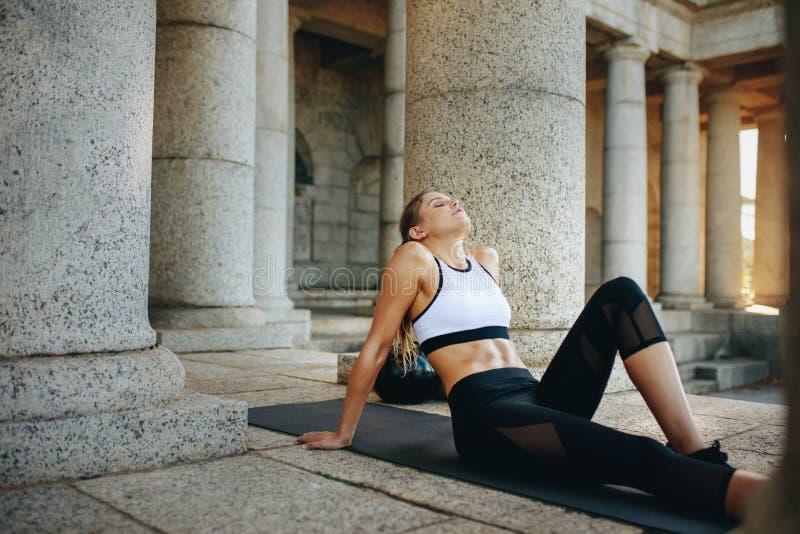 Die Eignungsfrau, die auf einer Ausbildungsmatte nach Training mit Augen sich entspannt, schloss Weiblicher Athlet, der das Eignu stockbild