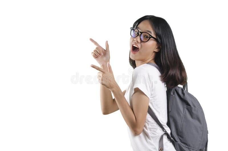 20, die eine asiatische junge hübsche Frau herausnahm und einen Rucksack mit weißem Hintergrund tragend stockbild
