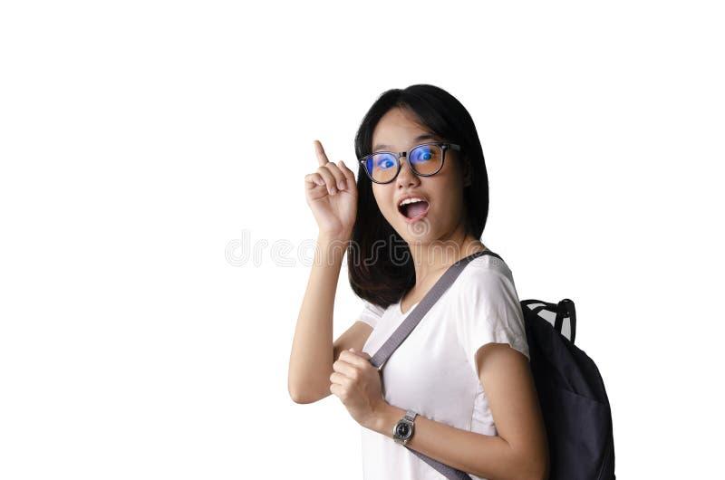 20, die eine asiatische junge hübsche Frau herausnahm und einen Rucksack mit weißem Hintergrund tragend lizenzfreies stockfoto