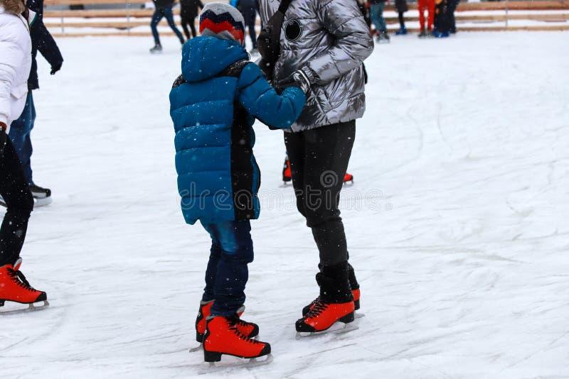 Die Eisbahn der Kinder Der Lehrer unterrichtet den Jugendlichjungen eiszulaufen Aktiver Familiensport während der Winterurlaube stockbild