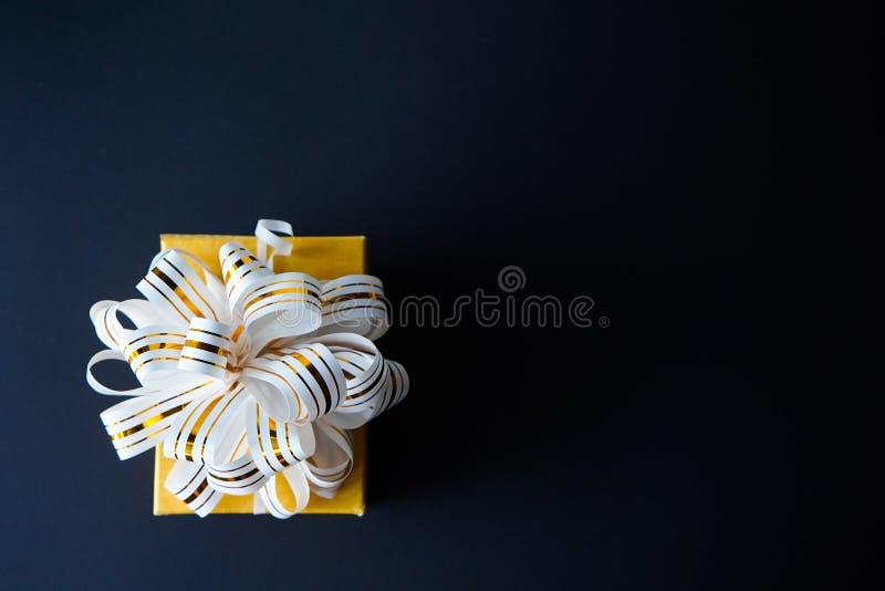 Die elegante Geschenkbox, die in wei?em und im Gold eingewickelt wurde, streifte Band auf schwarzem strukturiertem Hintergrund Ko lizenzfreie stockfotografie