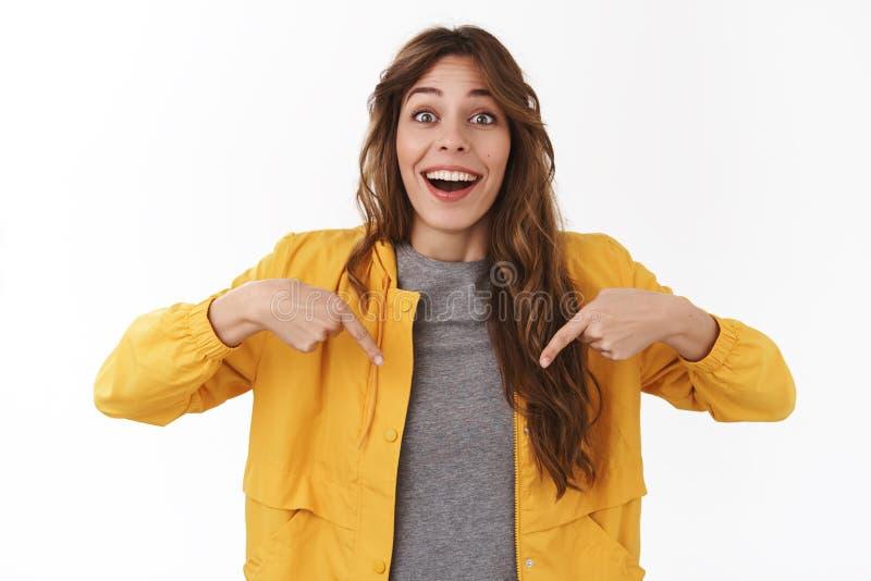 Die enthusiastische überraschte schöne junge Frau, die das aufgeregte erstaunte kühle Produkt unten zeigt reagiert, möchten es ha stockfoto