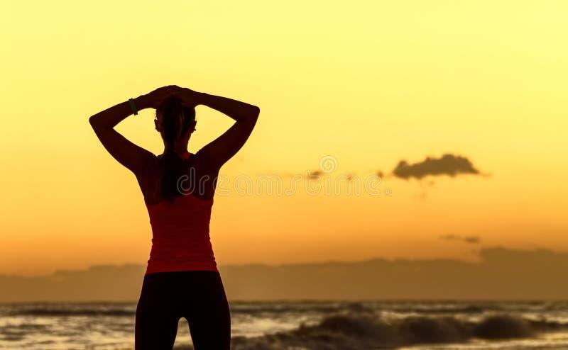 Die entspannte junge Frau, die im Sport steht, übersetzen auf Seeküste lizenzfreie stockfotos