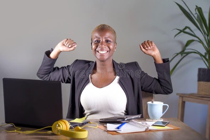 Die erfolgreiche schwarze afroe-amerikanisch Geschäftsfrau, die an lächelndem nettem steigendem Sieger des Büros arbeitet, bewaff lizenzfreie stockfotografie