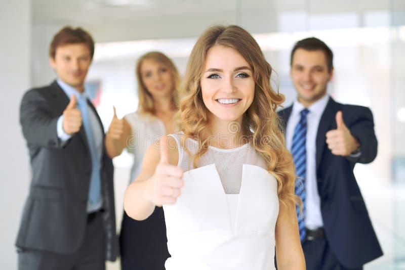 Die erfolgreichen jungen Geschäftsleute, die Daumen zeigen, up Zeichen lizenzfreies stockfoto