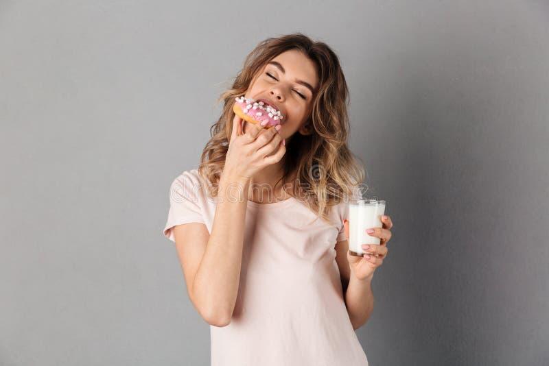 Die erfreute Frau im T-Shirt Donut essend und genießt stockfotos