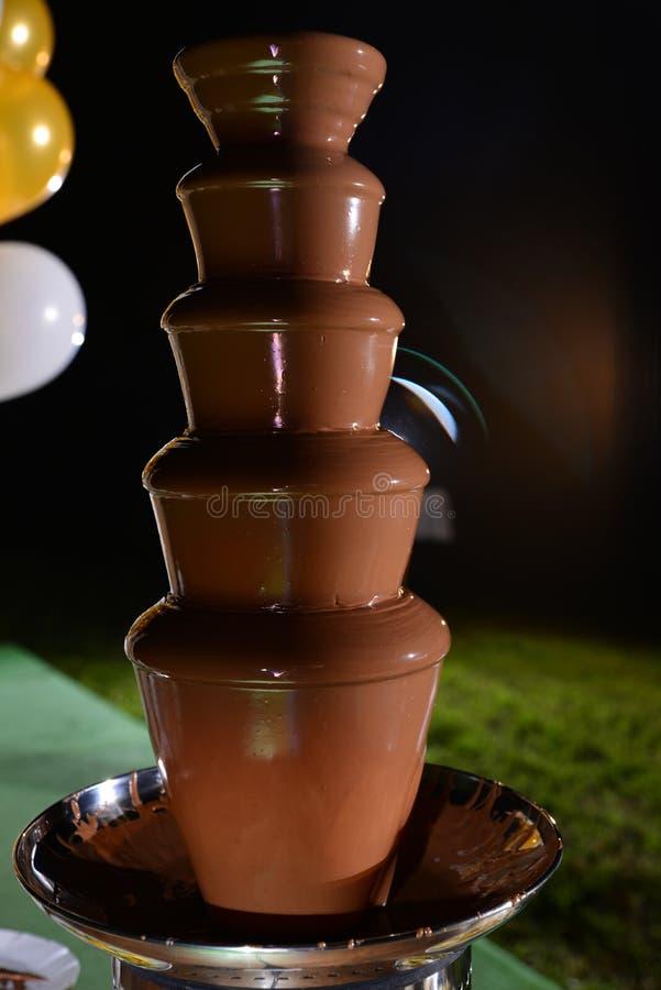 Die Ernte des Fruchtaufsteckspindelnstockes in Schokoladenbrunnenfondue legte auf eine Tabelle in Hotelrestaurant stockfotos