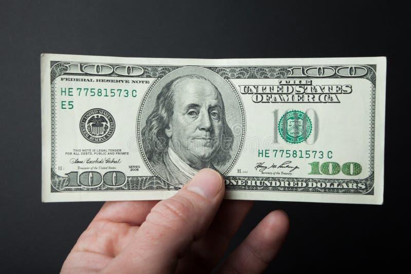 Die europäische Hand hält 100 Dollar auf einem schwarzen Hintergrund lizenzfreie stockbilder
