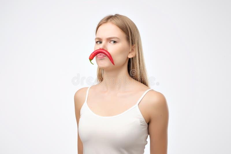 Die europäische junge Frau, die glühenden Paprikapfeffer hält, mögen Schnurrbart stockbild