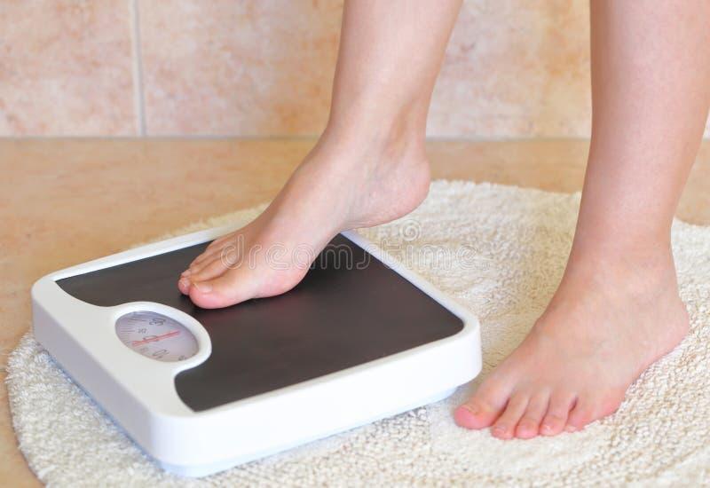 Die Füße der Frau auf Badezimmerwaage lizenzfreie stockbilder