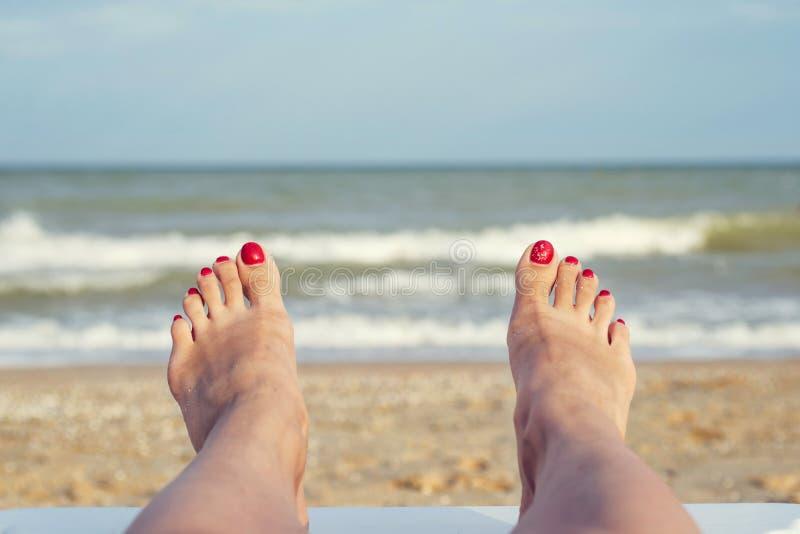 Die Füße der Frau auf dem Strand Weibliche Beine und Füße mit roten Nägeln sunbed an auf dem Strand Sommerentspannung auf Seehint lizenzfreies stockfoto