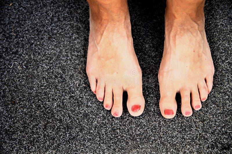 Die Füße der Frau auf einem grauen Hintergrund lizenzfreies stockfoto