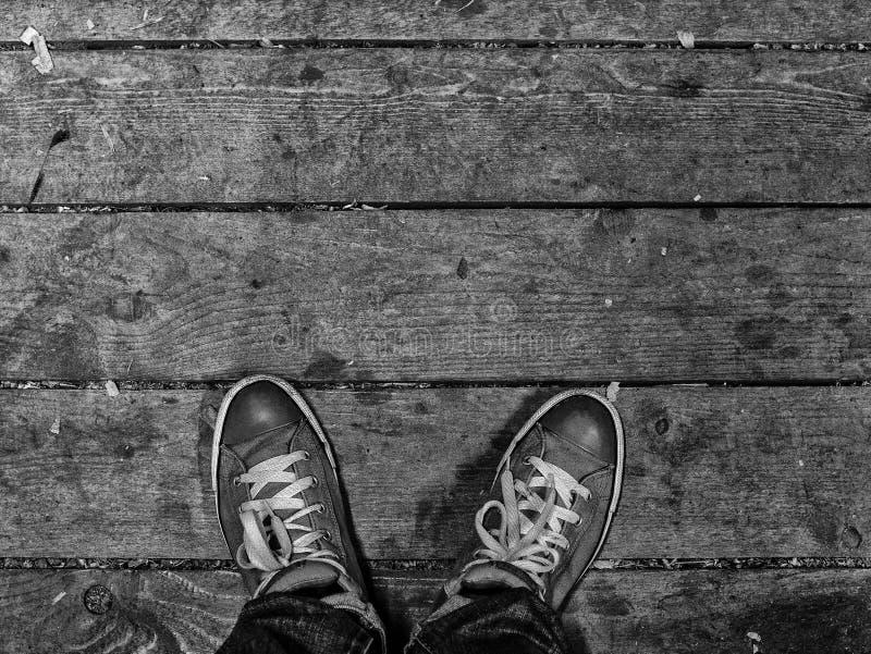 Die F??e der M?nner in den Turnschuhen stehen auf dem Bretterboden Die Turnschuhe der modernen M?nner Schwarzweiss-Foto Pekings,  lizenzfreies stockfoto