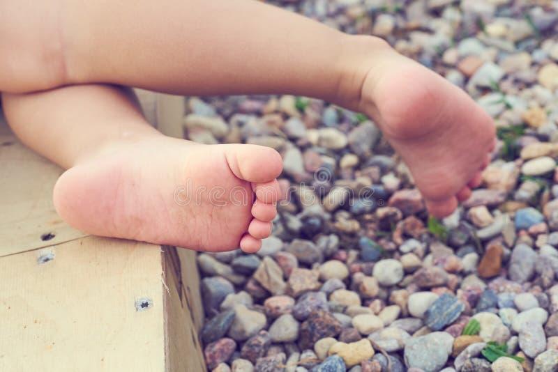 Die Füße des Babys einer kleinen Kindernahaufnahme auf dem Pebble Beach Ferien auf dem Mittelmeer stockfotos