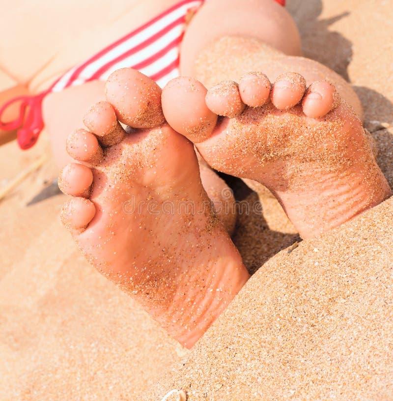 Die Füße des Kindes nah an dem sandigen Strand lizenzfreie stockfotografie