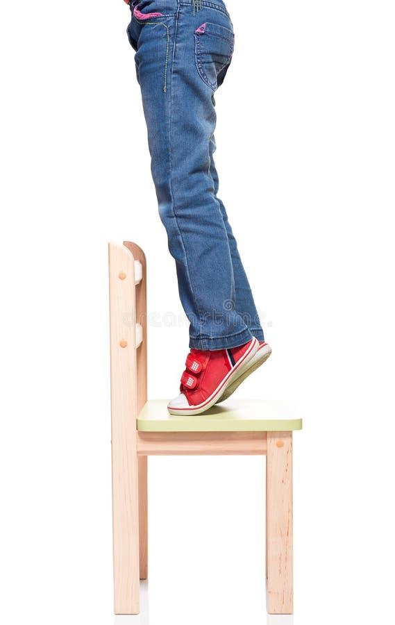 Die Füße des Kindes, die auf dem kleinen Stuhl auf Tiptoe stehen stockfotos